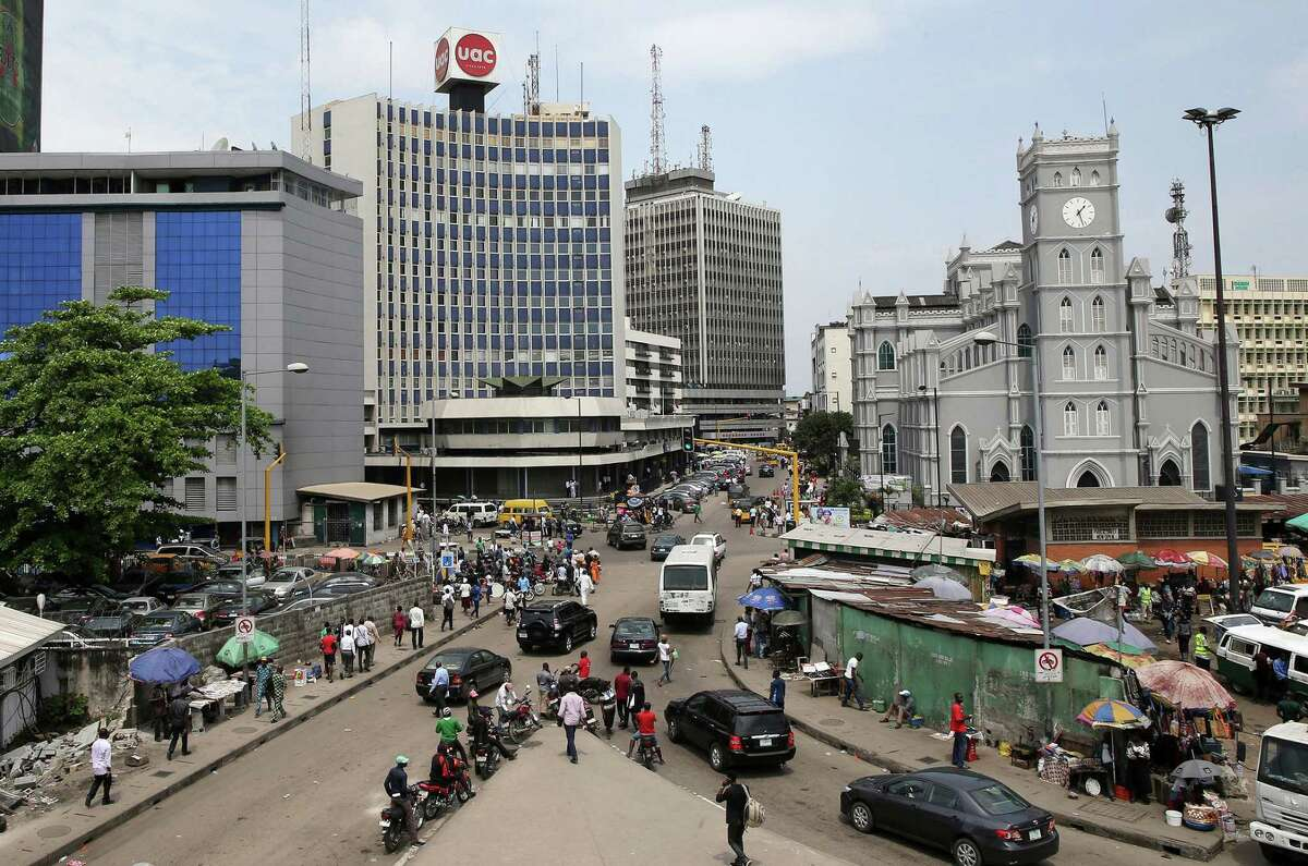 Pedestrians pass street traders in the business district of Lagos, Nigeria, on Oct. 26, 2015.
