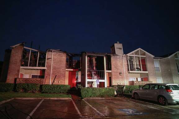 Firefighters clean up after battling a two-alarm fire overnight at an apartment complex on Flintlock Road near Castleford Street Thursday, May 11, 2017, in Houston. The fire destroyed four apartment units and damaged several more.
