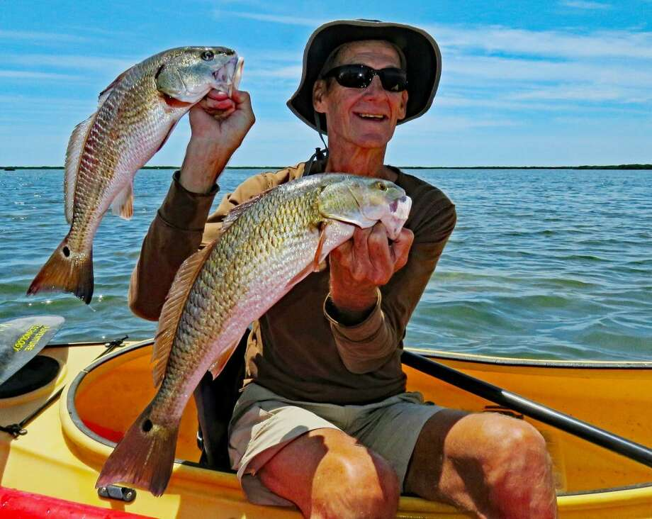 Fred Krebs of Fulton, who averages five days a week kayak fishing and has logged an estimated 7,000 miles of paddling over seven years, displays two keeper redfish on the east side of Brown & Root Flats. Photo: John Goodspeed / For The Express-News