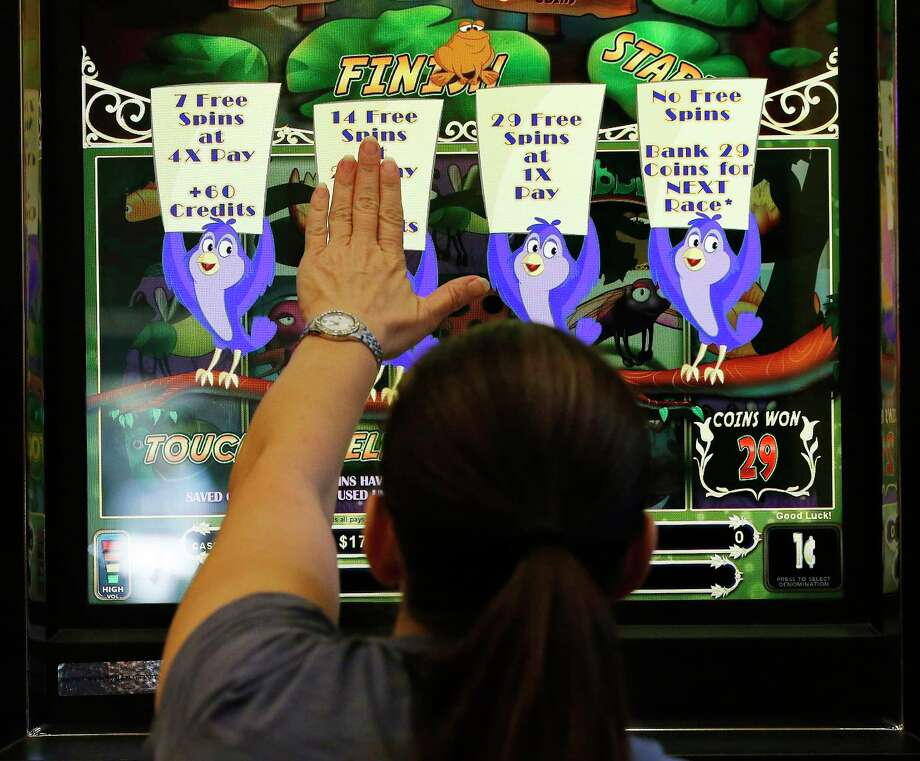"A gamer selects her options on a machine at Naskila Entertainment in Livingston, Texas on Tuesday, June 7, 2016. The Alabama Coushatta Indian Tribe in Livingston - about an hour north of Houston - reopened its casino after a 14-year closure prompted by threats from the state of Texas to take legal action against the tribe. Recent legal developments paved the way for the reopening. With 365 Class 2 electronic gaming devices, the former casino has been renamed Naskila Entertainment and its doors opened earlier this month to eager guests and gamers. Only ""bingo"" type machines are in use at Naskila Entertainment according to officials. (Kin Man Hui/San Antonio Express-News) Photo: Kin Man Hui, Staff / ©2016 San Antonio Express-News"