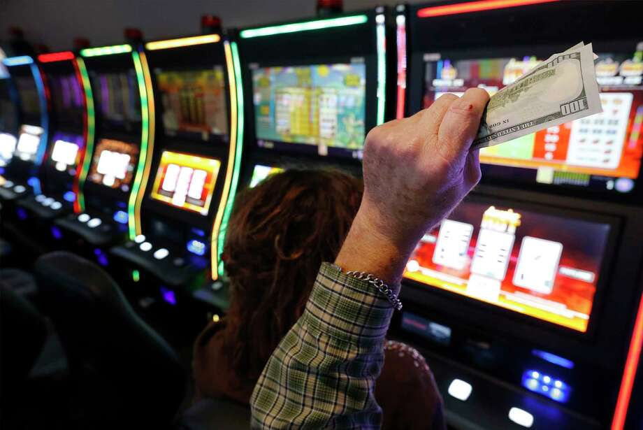 "With money in hand, Lufkin resident Tom Hudgens and his friend Jody Carrington play on a gaming machine at Naskila Entertainment in Livingston, Texas on Tuesday, June 7, 2016. Hudgens claimed he started with $20 and cashed out three times for winnings totalling a couple thousand dollars. The Alabama Coushatta Indian Tribe in Livingston - about an hour north of Houston - reopened its casino after a 14-year closure prompted by threats from the state of Texas to take legal action against the tribe. Recent legal developments paved the way for the reopening. With 365 Class 2 electronic gaming devices, the former casino has been renamed Naskila Entertainment and its doors opened earlier this month to eager guests and gamers. Only ""bingo"" type machines are in use at Naskila Entertainment according to officials. (Kin Man Hui/San Antonio Express-News) Photo: Kin Man Hui, Staff / ©2016 San Antonio Express-News"
