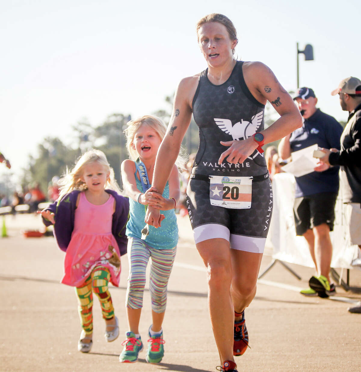 Triathlete Emily Finanger approaches the finish line as the first female finisher, joined by her daughters Kaia, 6, and Elin, 3, during the CB&I TRI - The Woodlands Triathlon on Saturday, May 6, 2017, at Northshore Park.