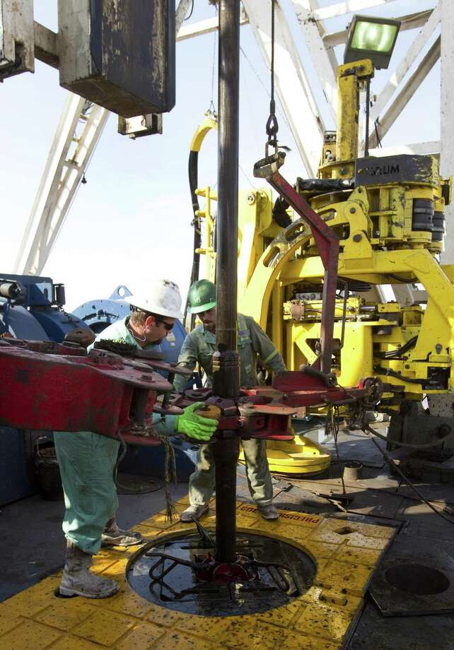 Two employees work on an Anadarko oil well in West Texas. The company announced Thursday that it is selling $625 million of Eagle Ford acreage. Photo: Houston Chronicle / © 2011 Houston Chronicle