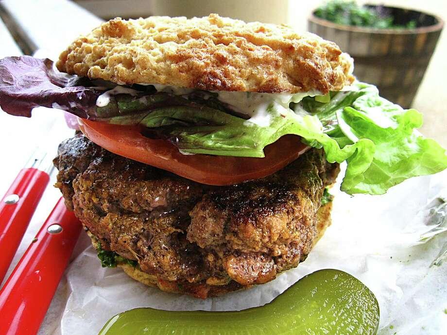 Bison burger with blue cheese, spinach pesto, lettuce, tomato and onions on a gluten-free sorghum bun from Red Bird Farmacy. Photo: Mike Sutter /San Antonio Express-News