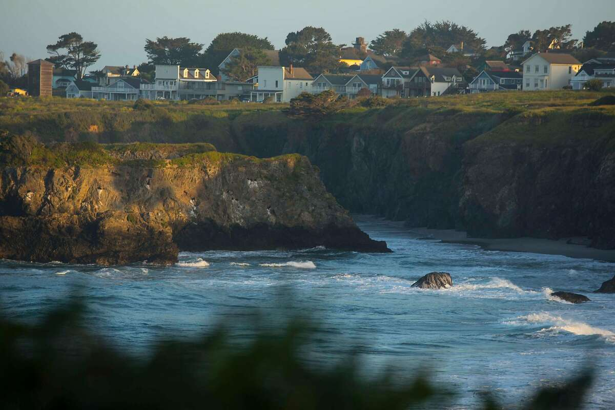 The sun rises over Mendocino Bay next to village of Mendocino in Northern California.