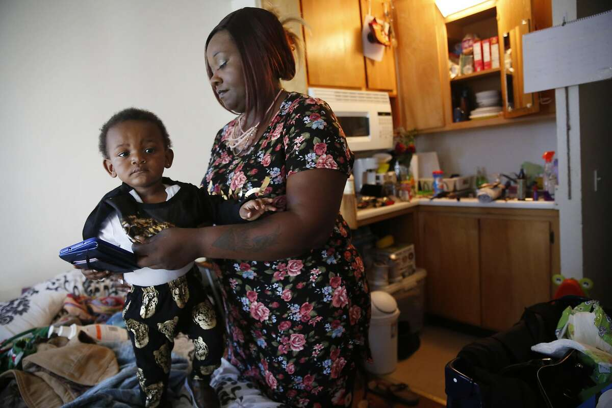 Jacquelynn Evans (right), who gets help from a program for homeless families to provide child care, readies herself and son Z'allah Evans (left), 21 months, to leave for work from their home at a SRO on Thursday, May 11, 2017 in San Francisco, Calif.
