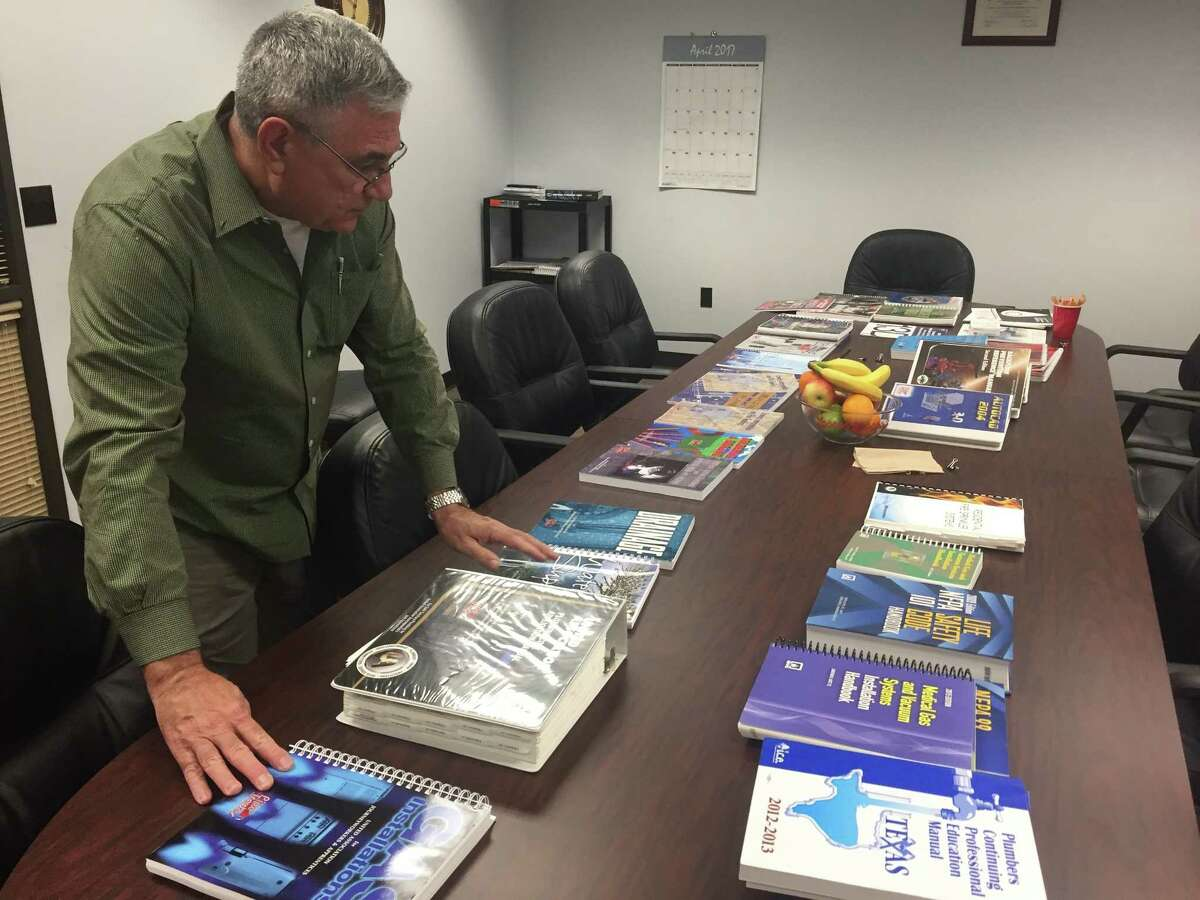 Robert Cross, director of training at the Plumbers Local Union 68 in Houston, shows the textbooks for the union's five-year training curriculum.