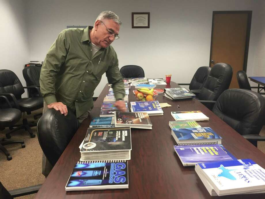 Robert Cross, director of training at the Plumbers Local Union 68 in Houston, shows the textbooks for the union's five-year training curriculum. Photo: Dylan Baddour