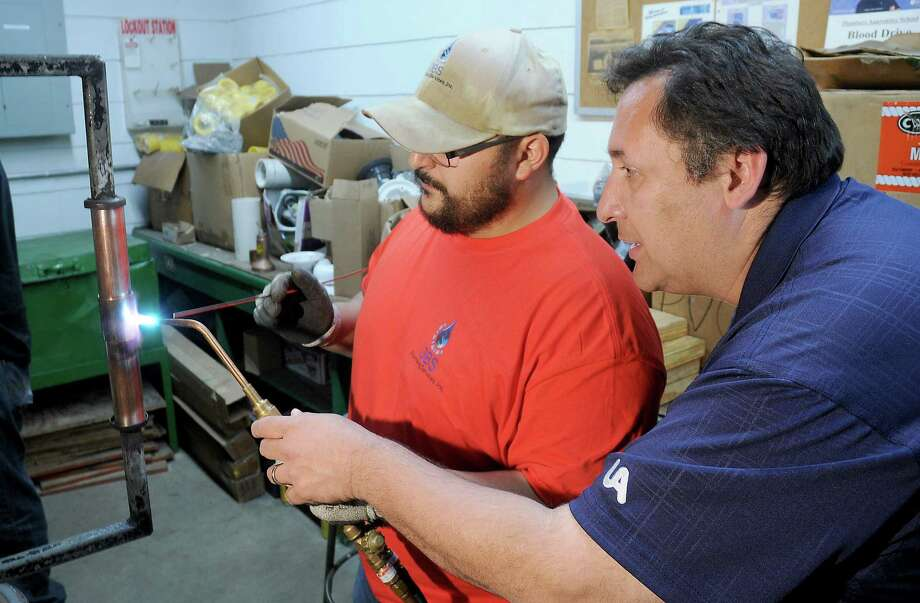 Training coordinator Othon Guillen shows student Carlos Rodriguez how to braze copper pipe during class at the Plumbers Local Union 68 Saturday April 22,2017.(Dave Rossman Photo) Photo: Dave Rossman, Freelance / Dave Rossman