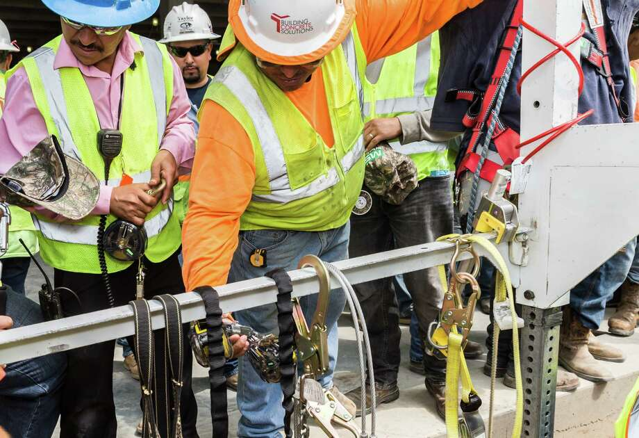 Construction workers inspect safety equipment in League City, Texas. Photo: Leslie Plaza Johnson, Freelancer / Freelance