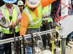 May 9, 2017:  Construction workers inspect safety equipment after having seen a demonstration on safety management at the MD Anderson construction site in League City, Texas.  (Leslie Plaza Johnson/Freelance)