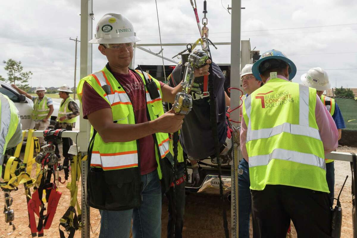 Construction workers inspect safety equipment after having seen a demonstration on safety management at the MD Anderson construction site in League City.