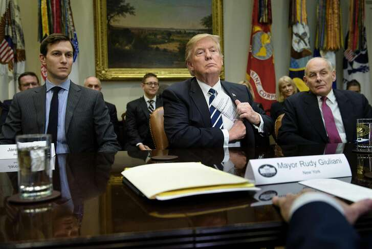 """(FILES) Senior Advisor Jared Kushner (L) and Secretary of Homeland Security John Kelly (R) listen while US President Donald Trump puts his papers away at the beginning of a meeting on cyber security in the Roosevelt Room of the White House January 31, 2017 in Washington, DC. While the new US president has shown a capacity to change, both his tone and his positions, he has been unable to show the world a """"new"""" Trump, with a steady presidential style and a clearly articulated worldview. As the symbolic milestone of his 100th day in power, which falls on April 29, 2017, draws near, a cold, hard reality is setting in for the billionaire businessman who promised Americans he would """"win, win, win"""" for them. At this stage of his presidency, he is the least popular US leader in modern history (even if his core supporters are still totally behind him.) / AFP PHOTO / Brendan Smialowski / TO GO WITH AFP STORY, US-politics-Trump-100days BRENDAN SMIALOWSKI/AFP/Getty Images"""