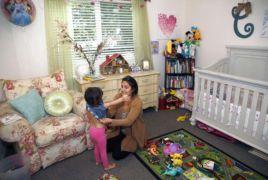 Natalie Ruiz dresses daughter Clara for preschool. Ruiz, 25, found out she was pregnant three weeks after moving into her dorm. Photo: Paul Chinn, The Chronicle