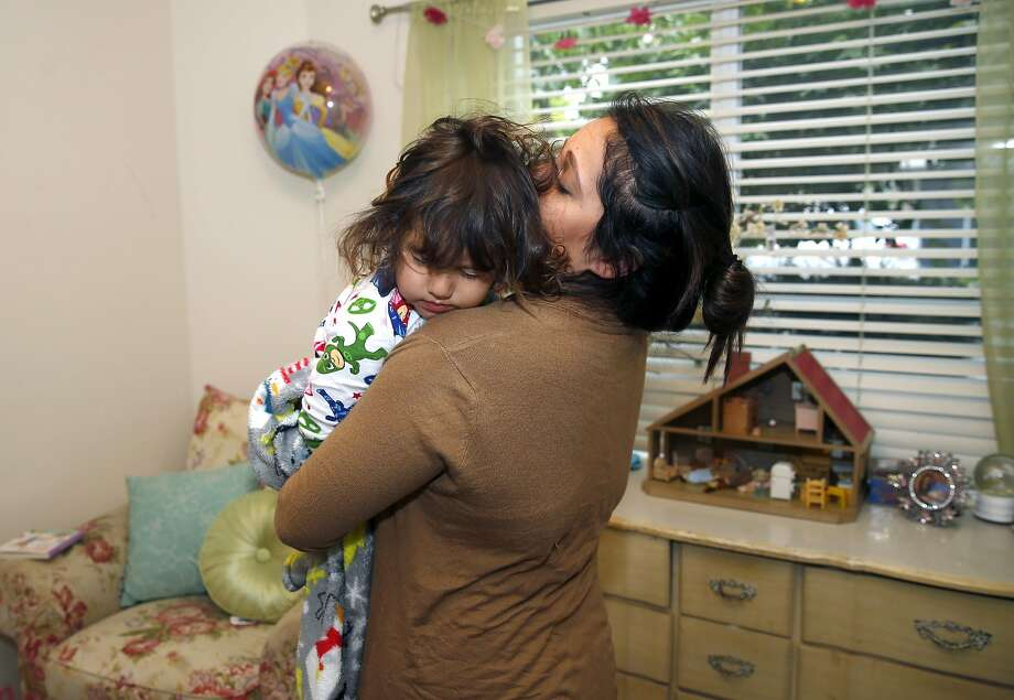Natalie Ruiz, who will deliver a speech to her graduating sociology class Sunday, awakens her 3-year-old daughter, Clara, in their apartment in Albany. Photo: Paul Chinn, The Chronicle