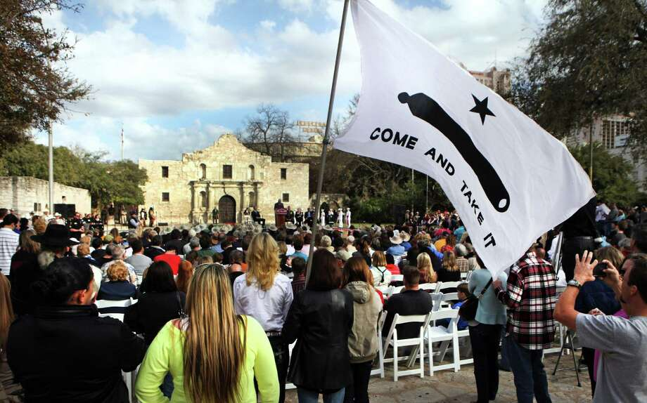 """The William Barret Travis Letter, requesting help to defend the Alamo, returned to the Alamo Feb. 23, 2013, for the first time since it was sent in 1836. Members of the Gonzales Chamber of Commerce hold a """"Gonzales Flag"""" during the ceremony. Photo: Bob Owen /San Antonio Express-News / © 2012 San Antonio Express-News"""