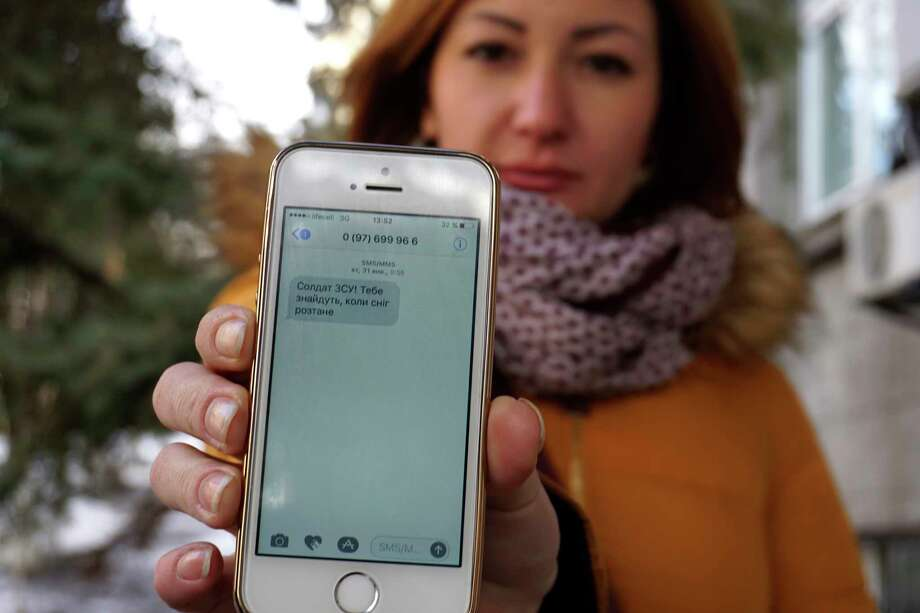 "Television journalist Julia Kirienko holds up her smartphone to show a text message reading ""Ukrainian soldiers, they'll find your bodies when the snow melts"" in Kiev, Ukraine. Ukrainian soldiers fighting pro-Russian separatists are being bombarded by threats and disinformation via text message. Photo: Raphael Satter, STF / Copyright 2017 The Associated Press. All rights reserved."
