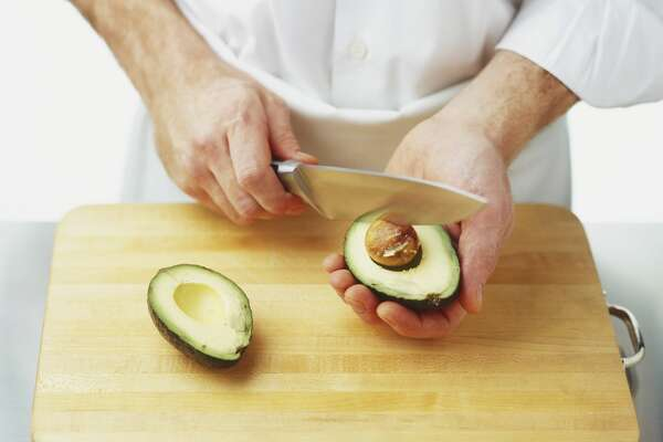 A man cutting an avocado with a knife.