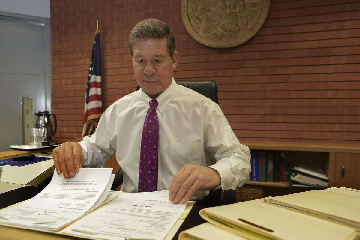 Superior Court Judge Robert Trentacosta looks through a court case at his courtroom in San Diego, CA, Thursday, 05/11/17, as additional case folders lie to his left. Trentacosta heads a commission that is advising the state to digitize their court cases.