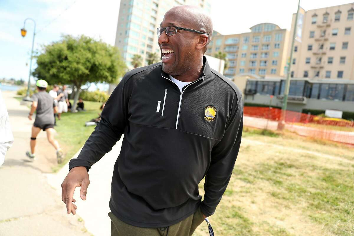 Golden State Warriors' interim head coach Mike Brown laughs after a group of young men filming a music video recognized him as he walked around Lake Merritt in Oakland, Calif., on Thursday, May 11, 2017.
