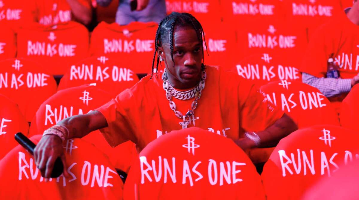 """Travis Scott tries to get fans to put on their """"Run as One"""" t-shirts before Game 6 of the second round of the Western Conference NBA playoffs at the Toyota Center, Thursday, May 11, 2017, in Houston."""