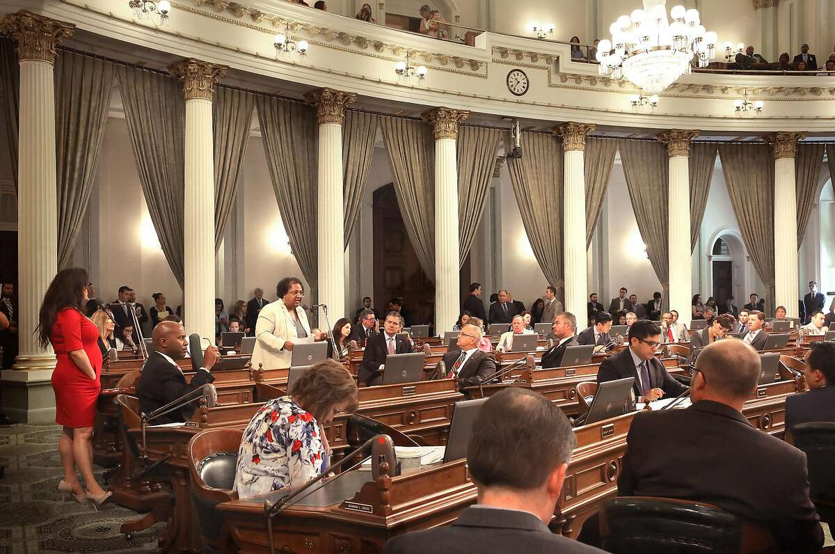 Assembly woman Lorena Gonzalez (wearing red at left), D-San Diego, listens to assembly woman Shirley N. Weber (in light jacket) as she speaks about importance of senate bill 277 passing at the California state capitol building in Sacramento, Calif., on Thursday, June 25, 2015.
