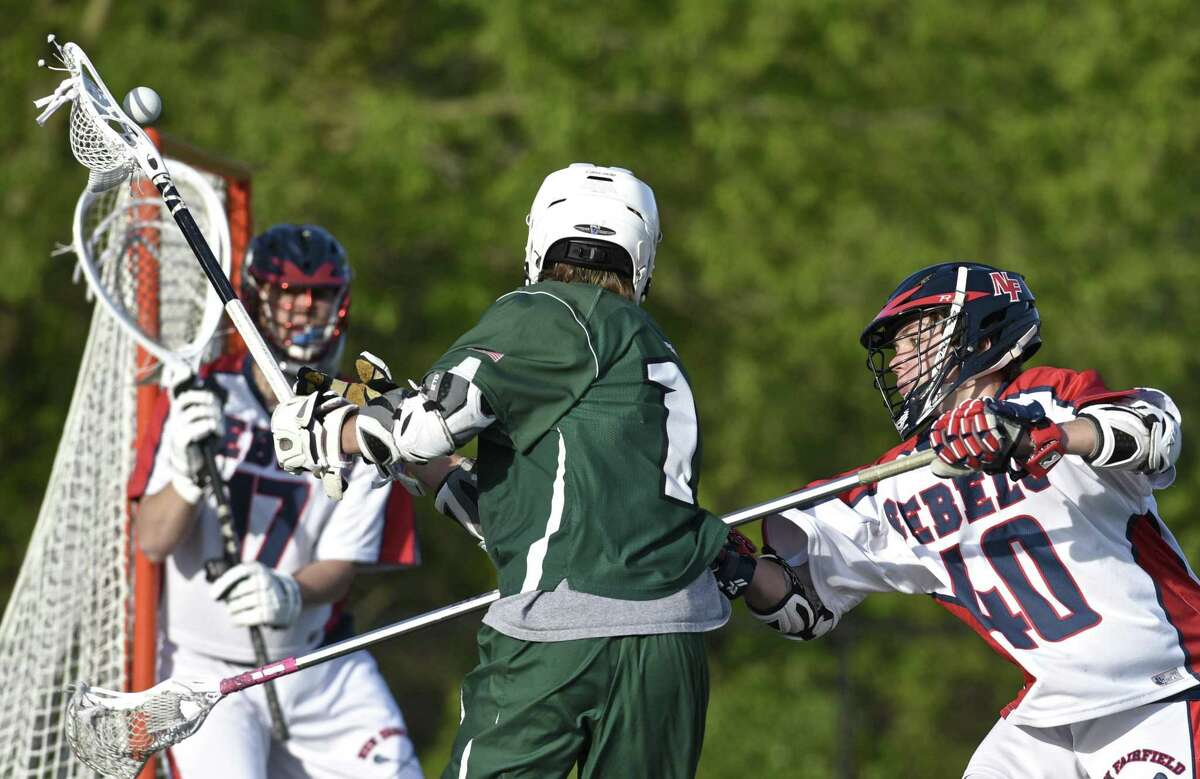 New Milford's William Gully (1) has the ball knocked away by New Fairfield's Nicholas Alviti (40) in the boys lacrosse game between New Milford and New Fairfield high school, on Thursday, May 11, 2017, at New Fairfield High School, in New Fairfield, Conn. New Fairfield Gabe Stein (17) is in goal.