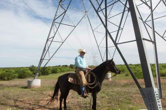 Rancher Richard Thorpe, owner of the Mesa T Ranch, poses underneath on of the towers installed on his land.