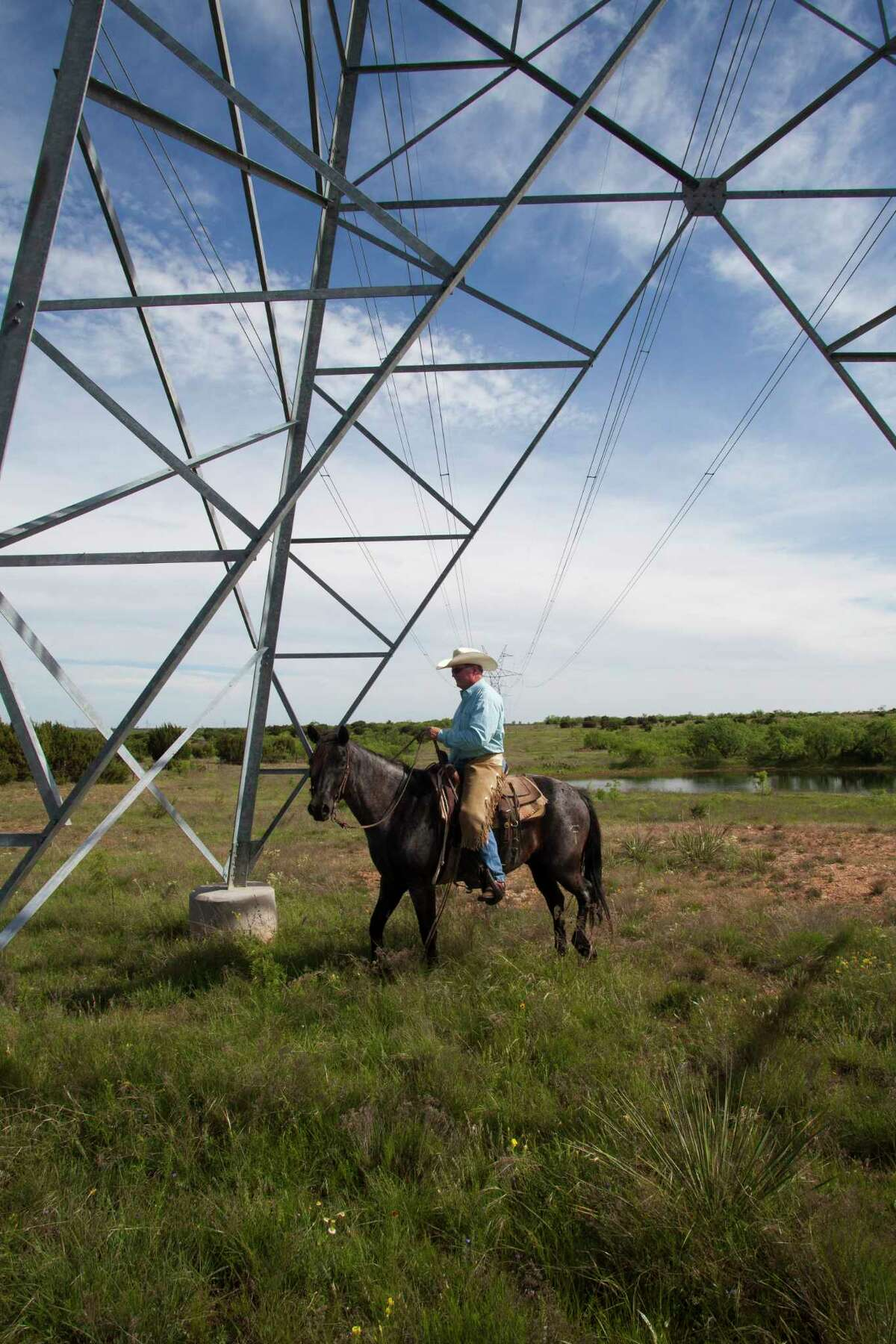 Rancher Richard Thorpe rides underneath an electric utility tower on his land just outside of Winters, TX.