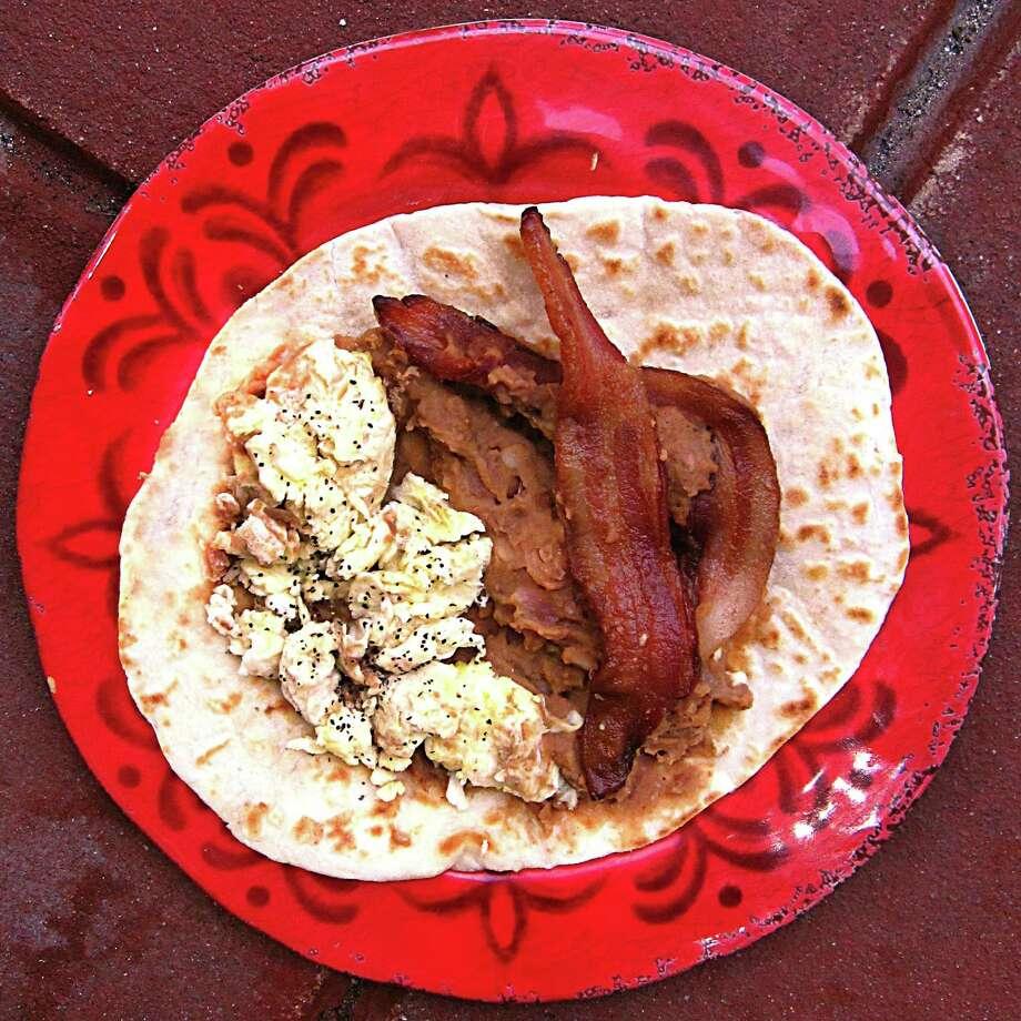 Bacon, egg and bean taco on a handmade flour tortilla from Eddie's Taco House. Photo: Mike Sutter /San Antonio Express-News