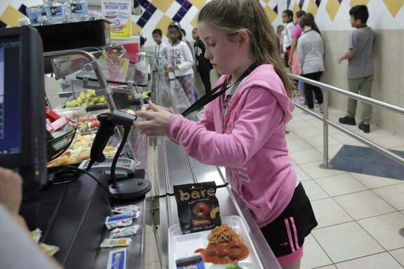 Hancock Elementary fourth grader Allison Irby pays for her lunch on Thursday, April 6, 2017, in Houston. The school offers a program where parents can put extra money in the funds so students who forget their lunch money get a full meal. ( Elizabeth Conley / Houston Chronicle )