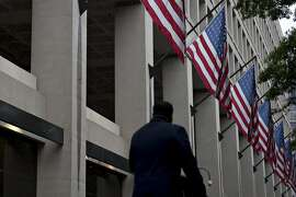 A pedestrian walks past American Flags hanging on display outside the Federal Bureau of Investigation (FBI) headquarters in Washington, D.C., U.S., on Thursday, May 11, 2017. President Donald Trump this week fired FBI Director James Comey amid the agency's investigation of Russian interference in last years election, saying the bureau needed new leadership to restore public trust and confidence. Photographer: Andrew Harrer/Bloomberg