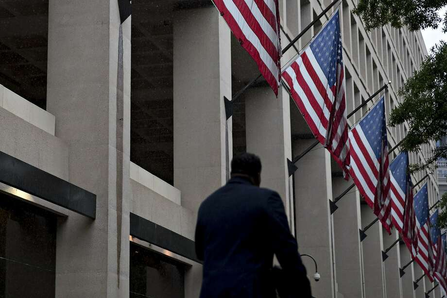 A man walks past American Flags hanging on display outside FBI headquarters in Washington, D.C. Photo: Andrew Harrer, Bloomberg