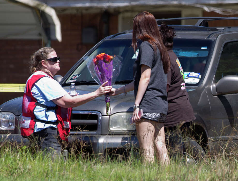 A family hands flowers to an emergency worker near the scene of a house fire that killed three children between the ages of 6 and 13 on Johnson Road, Friday, May 12, 2017, in the community of Tamina, just east of The Woodlands. The woman, who asked not to be identified, said she was in the area and heard of the fire before deciding to pick up flowers for the family. Five family members - a grandfather, grandmother, their son, their daughter, who was a mother of the three deceased children, and her fourth child, age 10  - were injured. Photo: Jason Fochtman/Houston Chronicle