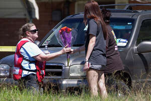 A family hands flowers to an emergency worker near the scene of a house fire that killed three children between the ages of 6 and 13 on Johnson Road, Friday, May 12, 2017, in the community of Tamina, just east of The Woodlands. The woman, who asked not to be identified, said she was in the area and heard of the fire before deciding to pick up flowers for the family. Five family members - a grandfather, grandmother, their son, their daughter, who was a mother of the three deceased children, and her fourth child, age 10  - were injured.