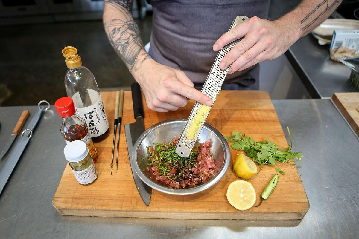Anthony Strong shaves some ginger into one of his new dishes, 90's style Ahi Crudo, for his new cooking venture Young Fava on Sunday, May 6, 2017 in San Francisco, Calif.