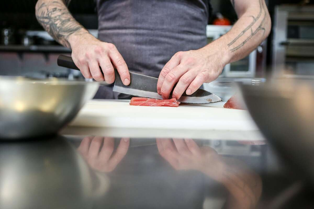Anthony Strong slices tuna as he prepares one of his newest dishes, 90's style Ahi Crudo, for his new cooking venture Young Fava on Sunday, May 6, 2017 in San Francisco, Calif.