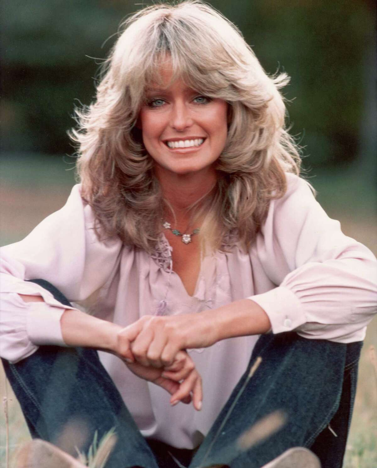 Publicity portrait of American actor and model Farrah Fawcett smiling while sitting outdoors in blue jeans and a mauve blouse. (Photo by Hulton Archive/Getty Images)