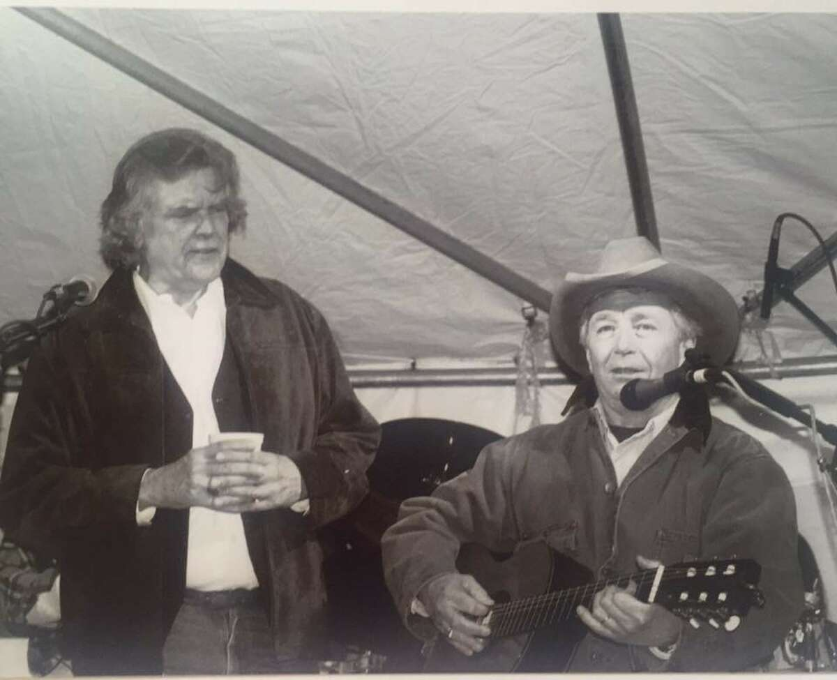 Attorney Dick DeGuerin performs at his 60th birthday, February 2001, as singer-songwriter Guy Clark looks on. DeGuerin performed Clark's
