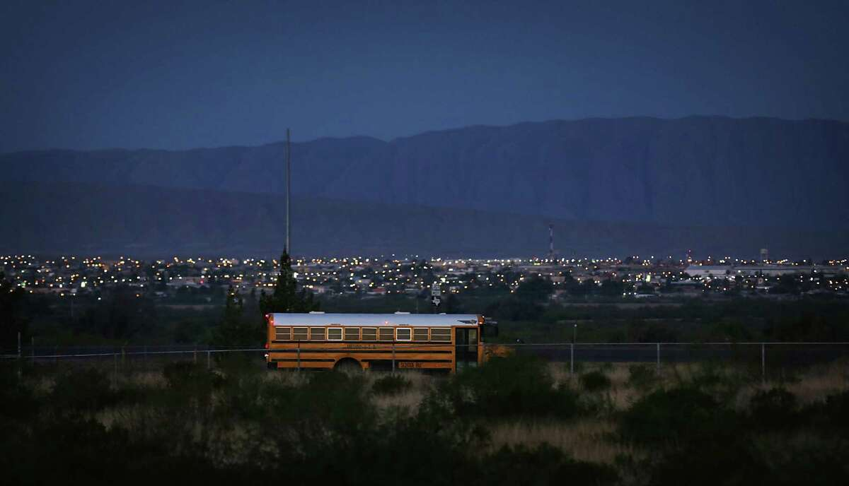 A School bus makes the rounds picking up students in Presidio, TX, with the lights of Ojinaga, Mexico in the back ground.