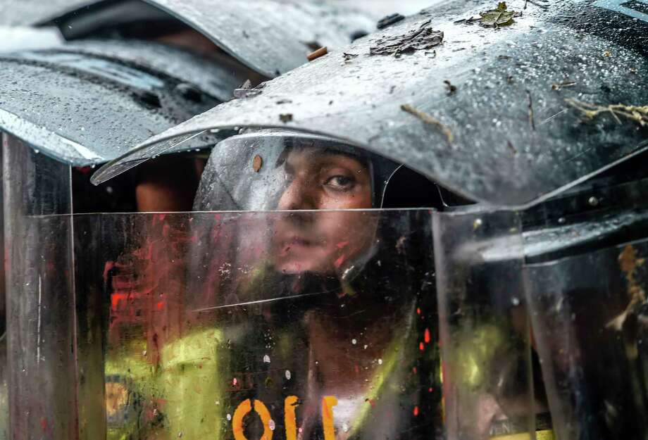 Riot police take cover behind their shields as they clash with opposition activists during a protest against the government in Caracas Friday.  Photo: JUAN BARRETO, Staff / AFP or licensors