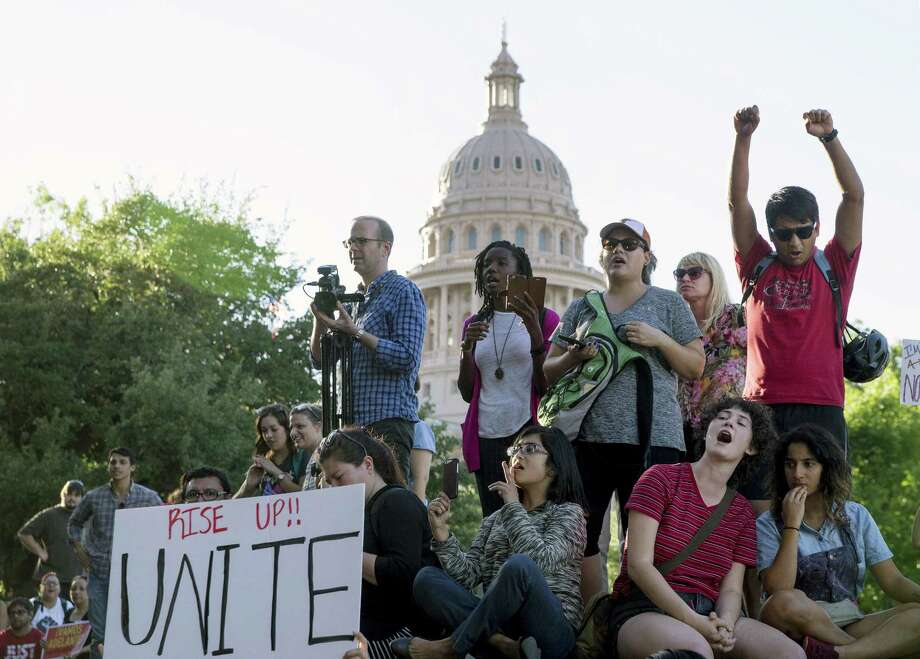 Protesters against the Senate Bill 4 sanctuary cities ban rally May 1 outside the Texas Department of Insurance building where Republican Gov. Greg Abbott has an office in Austin. The ACLU is representing clients in federal court challenging the measure. Photo: Jay Janner /Associated Press / Austin American-Statesman