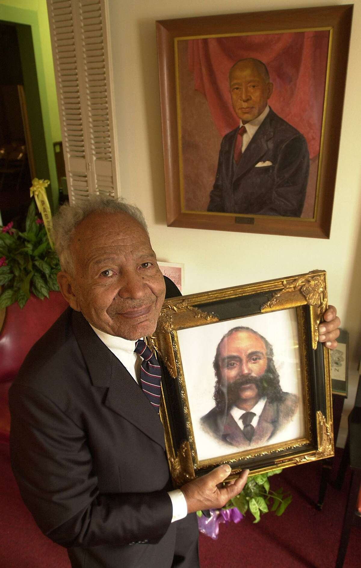 Sutton's Paradise Funeral Home owner A.C. Sutton holds a picture of his grandfather, Samuel Wesley Sutton, in 2001 as he poses in front of a picture of his father, Samuel Johnson Sutton.