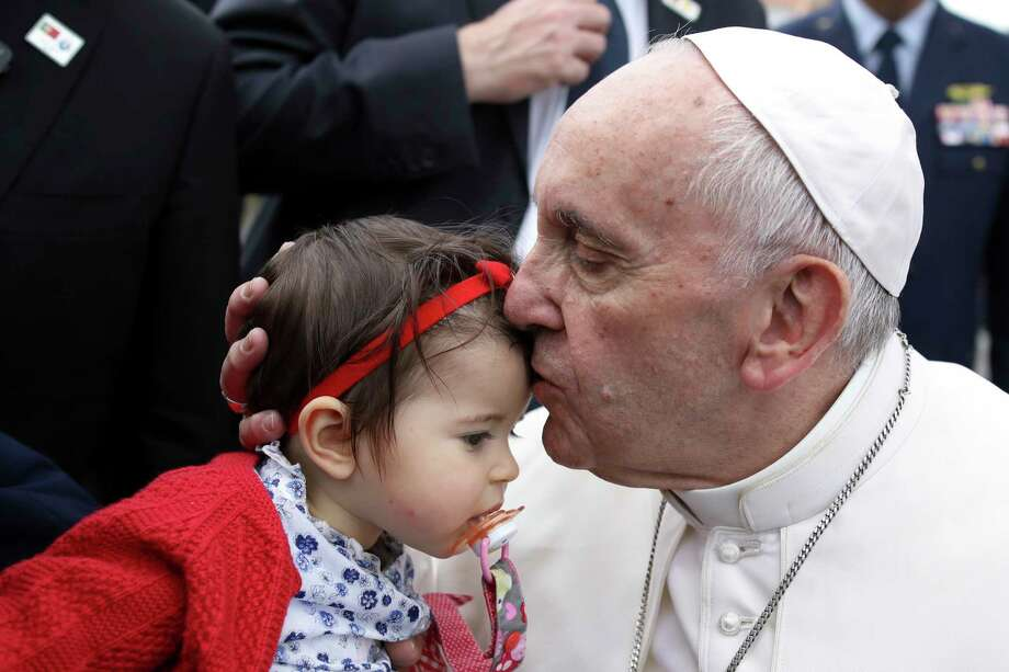Pope Francis kisses a child as he arrives Friday in Leiria, Portugal. Photo: Paulo Cunha, POOL / AP