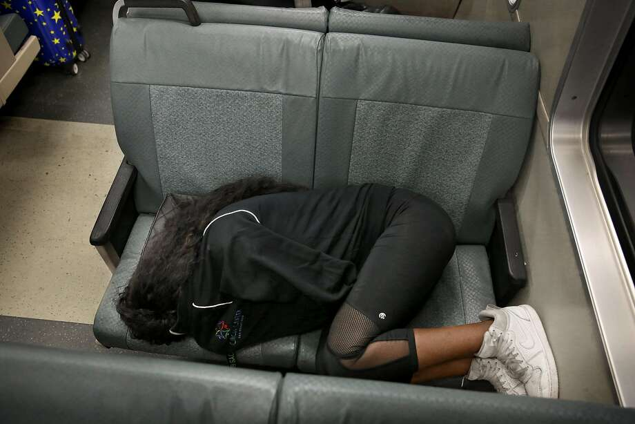 """A BART passenger sleeps on a seat at Powell Street Station. Some directors bristled at the """"one-ticket, one-seat"""" ordinance and wanted police to rethink it. Photo: Liz Hafalia, The Chronicle"""