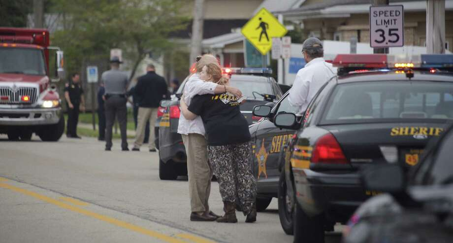 People hug outside Pine Kirk nursing home in Kirkersville, Ohio on Friday.  Authorities say Kirkersville Chief Steven Eric Disario and two nursing home employees were killed by a gunman who was later found dead inside the facility. Photo: Tom Dodge, MBO / 2017 The Columbus Dispatch