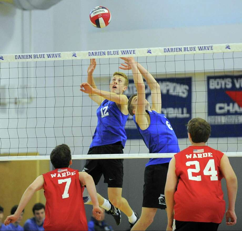 Darien's Tim Herget (12) plays the ball off the set of Tyler Hergert at the net in front of Fairfield Warde's Guilherme Lima (7) and Owen Edminster during their game Friday at Darien High School. Darien defeated Fairfield Warde 25-16, 25-15, 25-14. Photo: Matthew Brown / Hearst Connecticut Media / Stamford Advocate