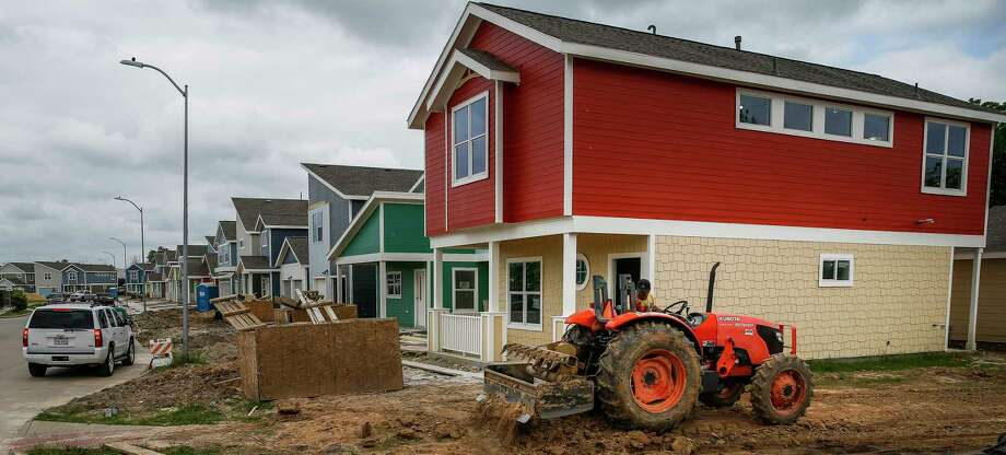 A tractor moves dirt around a home under construction in the Avenue Place affordable housing neighborhood Tuesday, April 25, 2017 in Houston.  Click through the gallery to see what you need to earn to buy a house in Houston.  Photo: Michael Ciaglo, Houston Chronicle / Michael Ciaglo