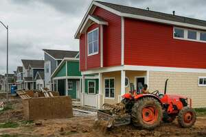 A tractor moves dirt around a home under construction in the Avenue Place affordable housing neighborhood Tuesday, April 25, 2017 in Houston. The city of Houston has wasted, misspent or lost track of tens of millions of affordable housing dollars over the last decade.
