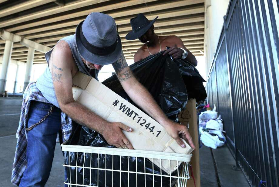 Edwin Ford, right, and Roy Dailey are packing up their belongings into a small cart in preparation for moving from underneath the overpass of U.S. 59 at Congress Ave. Friday.  Photo: Yi-Chin Lee, Staff / © 2017  Houston Chronicle